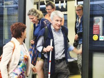 Slechtziende reiziger met witte stok stapt van een tram