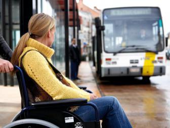rolstoelgebruiker wacht op de bus die in de achtergrond aankomt