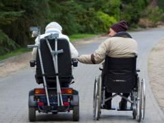 twee rolstoelgebruikers zijn samen op pad